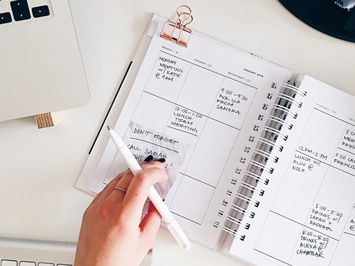 Woman writing in daily planner with a laptop nearby