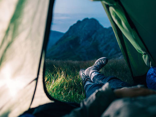 Person laying their tent with feet outside facing a mountain