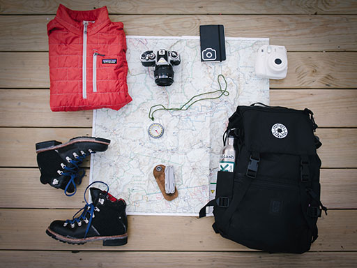 A red vest, hiking boots, backpack, and other camping items displayed over a map