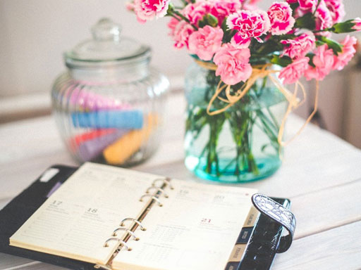 A daily planner with a vase and glass jar in the background