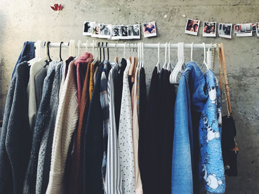 Clothes on rack and photos on wall