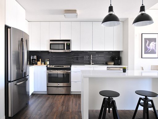 Modern kitchen with white cabinets, stainless steel fridge, and black accents