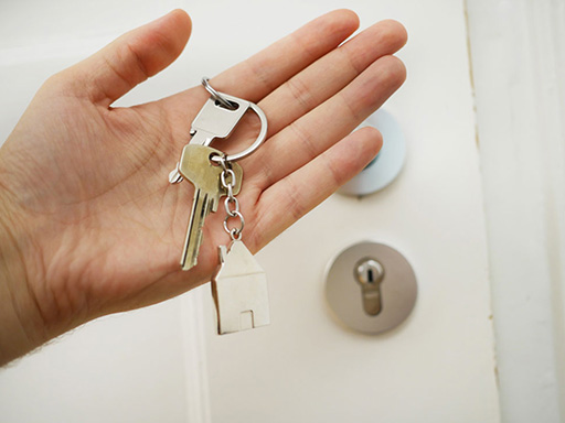 Hand holding a house key in front of a padlocked door
