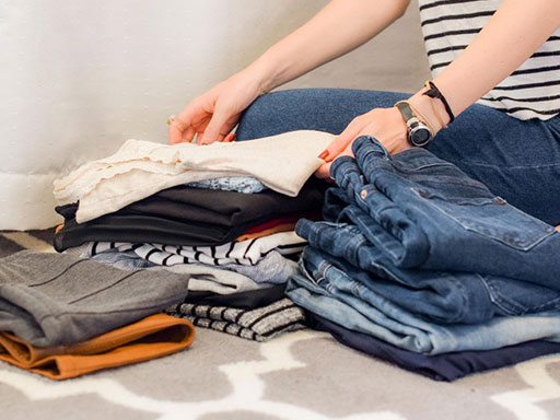 Girl in a striped shirt sorting her clothes on the floor