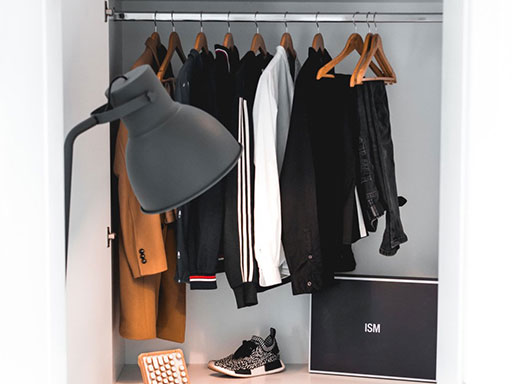 A closet with a dresser and chair inside of it