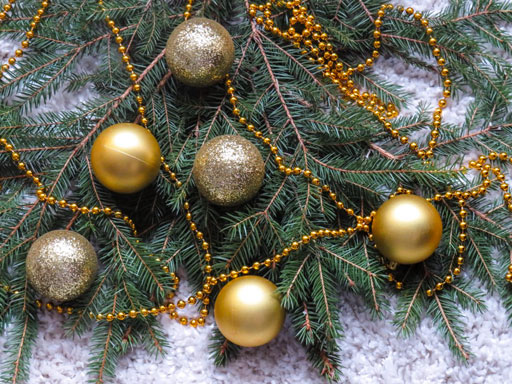 Gold ornaments and garland on pine branches