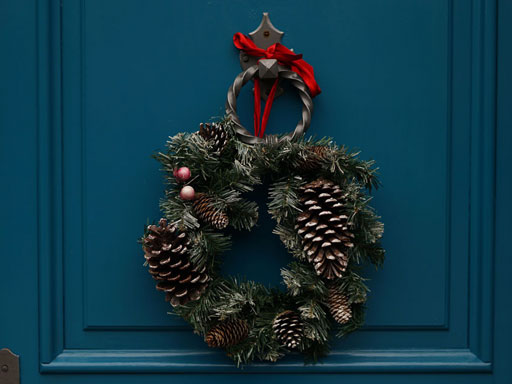 A pinecone and pine wreath hanging on a blue door